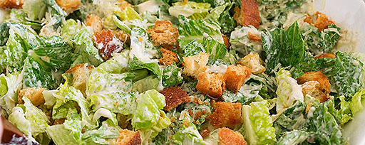 Caesars salad with bacon bits and real bacon